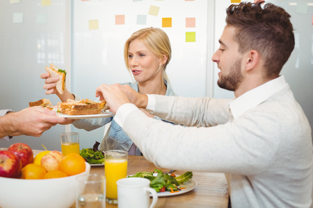 fruits juice: Cropped image of businessman serving sandwiches as colleagues taking it during lunch in creative office