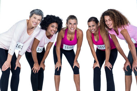 standing against: Portrait of smiling athletes bending while standing against white background Stock Photo