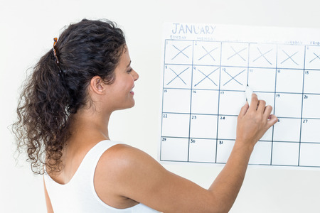 marking: Smiling pregnant woman marking off dates on calendar against white background