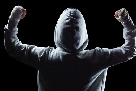 Rear view of winner in hood with arms raised against black background