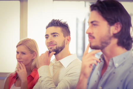 day dreaming: Business people day dreaming with hand on chin in creative office Stock Photo