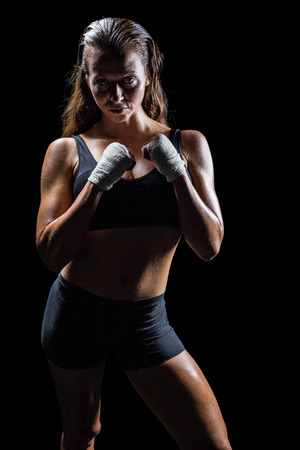 fighting stance: Portrait of female athlete with fighting stance against black background Stock Photo