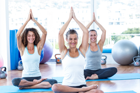 joined: Women doing lotus pose with hands joined overhead in fitness studio