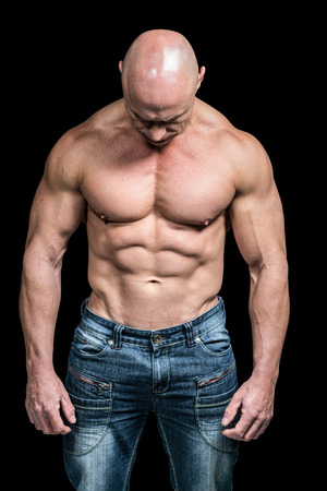man looking down: Muscular sad man looking down while standing against black background
