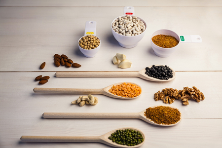 pulses: Spoons and cups of pulses and seeds on wooden table