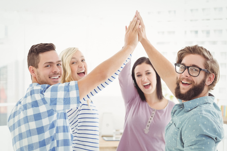 winning business woman: Portrait of smiling business people giving high five at office Stock Photo
