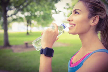 refreshment: Side view of smiling jogger woman drinking water while standing in park