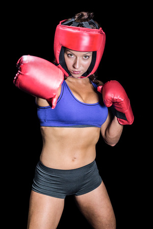 fighting stance: Portrait of pretty boxer with fighting stance against black background