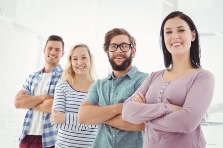 Portret van lachende mensen uit het bedrijfsleven staan in de rij met armen gekruist op kantoor Stockfoto
