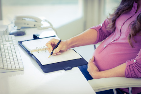 Midsection of pregnant businesswoman writing on diary at desk in home office Stock Photo