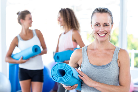 mat: Portrait of woman holding yoga mat in fitness studio