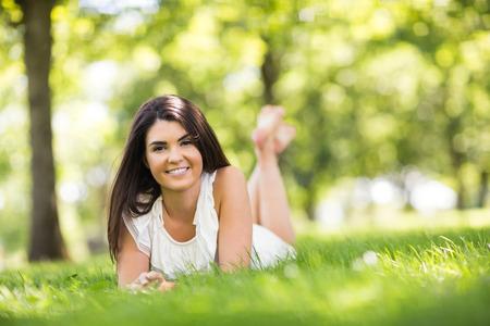 grassland: Portrait of beautiful woman lying on grassland in park