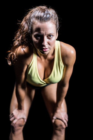 bending: Portrait of exhausted athlete bending against black background Stock Photo
