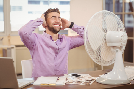 electric fan: Relax businessman sitting at desk with electric fan in office