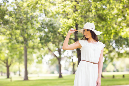 sun hat: Confident young woman holding sun hat while standing on grassland in park