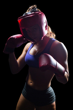 fighting stance: Portrait of female fighter with fighting stance against black background