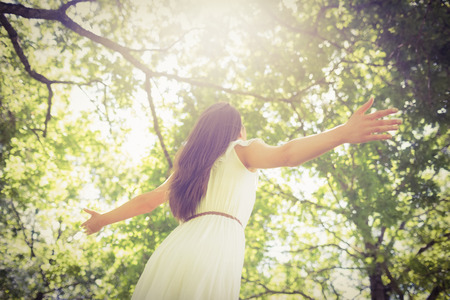 long hair woman: Low angle view of long hair woman with arms outstretched against trees