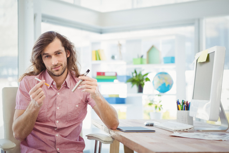 artistic addiction: Portrait of hipster holding cigarettes at desk in office