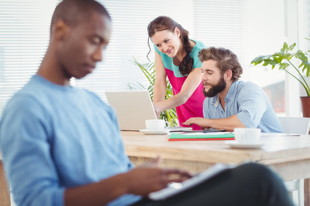 persona seduta: Woman pointing at laptop while discussing with man at desk with person sitting on foreground Archivio Fotografico