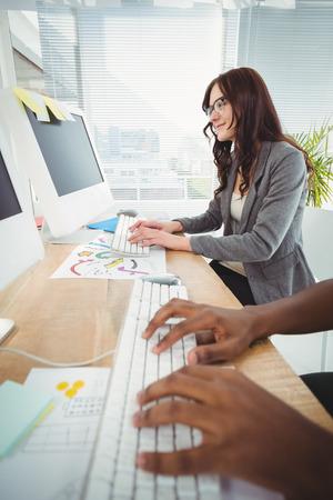 teclado: Manos recortadas al escribir en el teclado en el escritorio del ordenador con la empresaria en la oficina