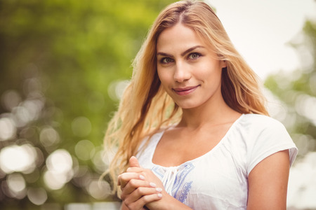 hands clasped: Portrait of smiling woman with hands clasped while standing in park Stock Photo
