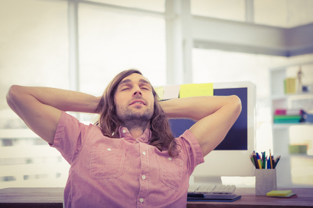 hands behind head: Hipster with hands behind head resting at computer desk in office