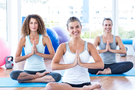 joined: Portrait of cheerful women with hands joined in fitness studio Stock Photo