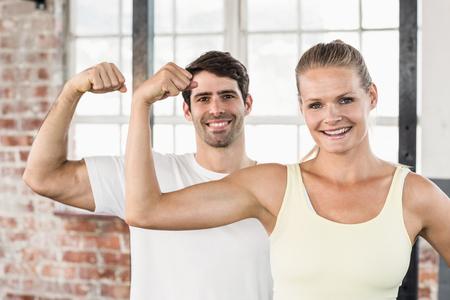 flexing: Portrait of couple flexing muscles in crossfit gym