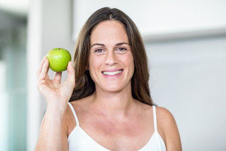 granny smith: Portrait of pregnant woman holding Granny Smith in room