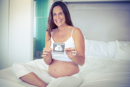 ultrasound scan: Portrait of happy woman with ultrasound scan sitting on bed