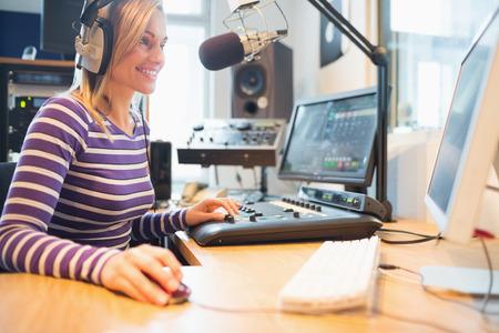 microfono de radio: Feliz locutor de radio femenina que usa el ordenador mientras la radiodifusión en el estudio Foto de archivo