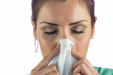 blowing nose: Close-up of woman suffering from blowing nose with tissue on mouth against white background