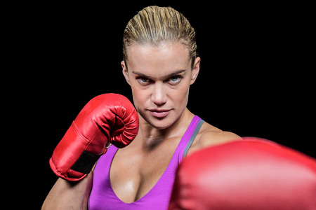 fighting stance: Portrait of female boxer with fighting stance against black background