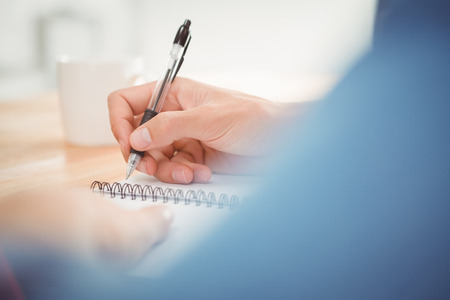 person writing: Cropped image of man writing on spiral book at desk in office Stock Photo