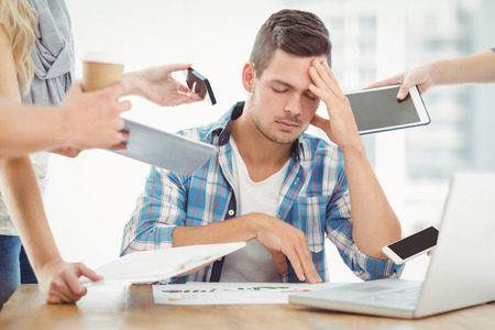 depression man: Depressed businessman with head in hand while sitting at desk Stock Photo