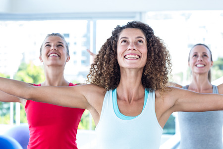 fit women: Fit women looking up and smiling with arms outstretched in fitness studio