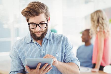 eyeglasses: Man wearing eyeglasses using digital tablet while standing at office