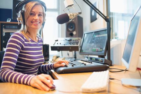 Portrait of female radio host using computer while broadcasting in studio