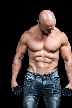 free weight: Bodybuilder exercising with dumbbells against black background