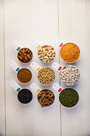 lima bean: Portion cups of pulses seeds and nuts on wooden table Stock Photo