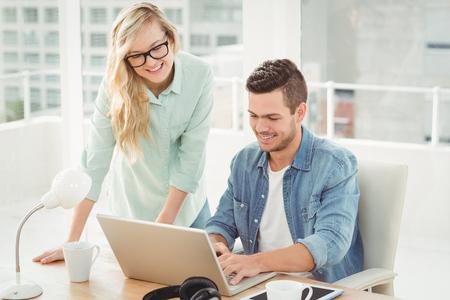 若い男と女が着て眼鏡を机にノート パソコンで作業しながら笑みを浮かべてください。