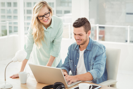 Smiling young man and woman wearing eyeglasses while working on laptop at desk