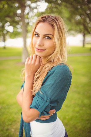 hand on the chin: Portrait of beautiful woman with hand on chin while standing on grass at park