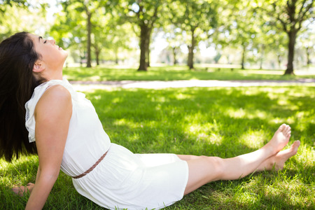 Pretty woman relaxing with eyes closed while sitting on grassland Stock Photo