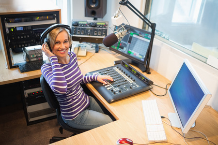 Portrait of happy female radio host at sound mixer desk in studio Imagens - 45552176