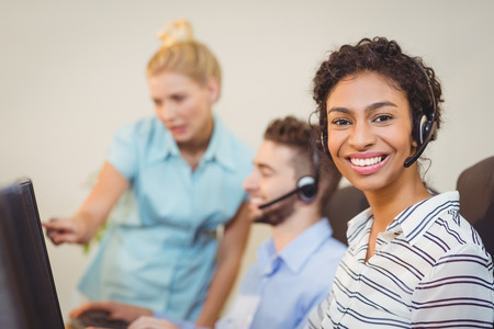 on call: Portrait of female employee with coworkers working in call center