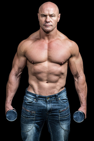 free weight: Portrait of bodybuilder holding dumbbells against black background