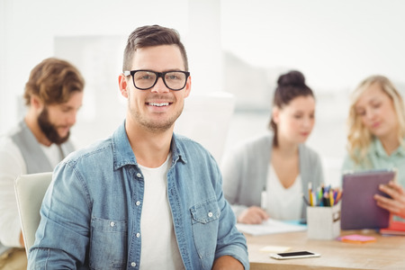 Portrait of smiling man wearing eyeglasses with people working at office