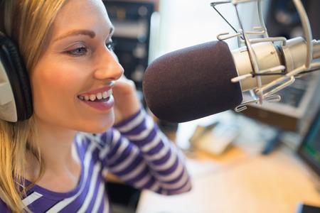 microfono de radio: Primer plano de la radiodifusión locutor de radio femenina joven feliz en estudio