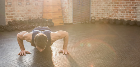 push ups: Handsome man doing wide arm push ups at the gym